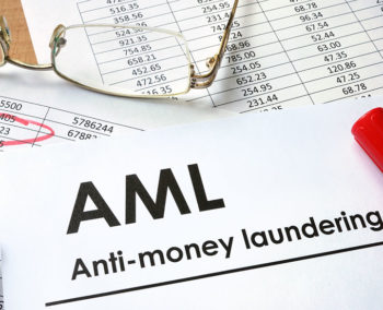 Anti-money laundering text with numbers spreadsheet in background on table