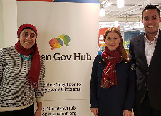 Open Gov Hub director and guests in front of Open Gov Hub banner with logo